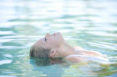 Femme qui se relaxe dans la piscine